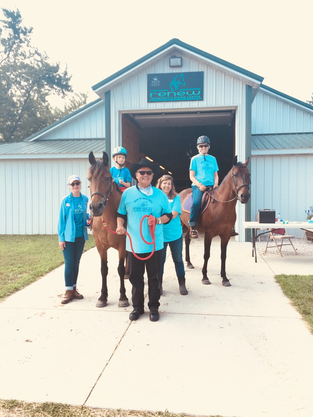 A group of people with horses in front of Renew